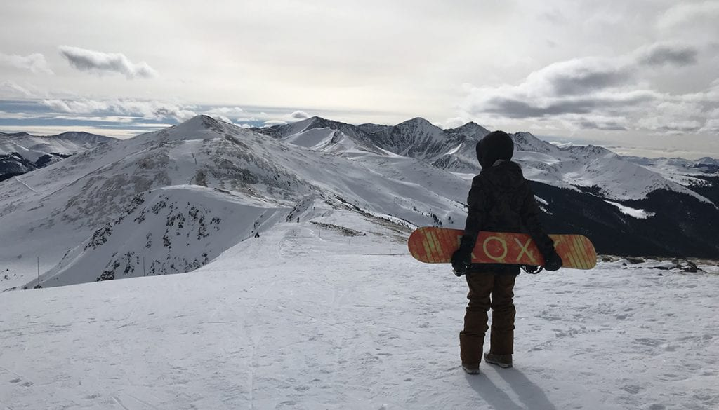 Stephanie-Kemp-on-top-of-Peak-6-holding-snowboard
