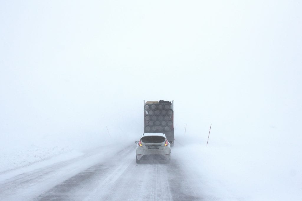 (white car behind a truck on snowy road)